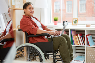 woman in wheelchair using a laptop in front of a bookshelf